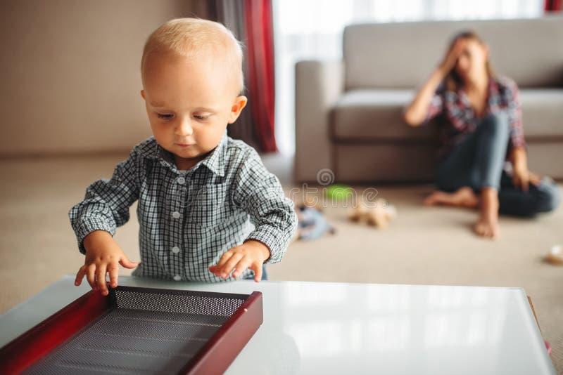 Μικρά παιδικά παιχνίδια, τονισμένη μητέρα στο υπόβαθρο στοκ εικόνα