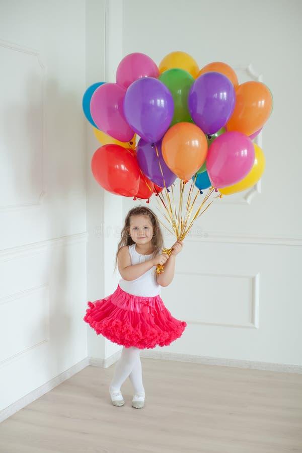 Μικρά παιχνίδια κοριτσιών με τα ζωηρόχρωμα μπαλόνια στο στούντιο στοκ φωτογραφία με δικαίωμα ελεύθερης χρήσης