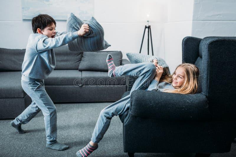 Μικρά παιδιά στις πυτζάμες που έχουν την πάλη μαξιλαριών στο σπίτι στοκ εικόνες