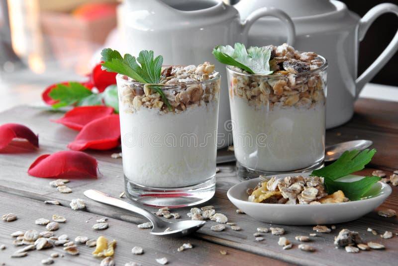 Μικρά ποτήρια του σαφούς γιαουρτιού με το muesli στοκ φωτογραφίες