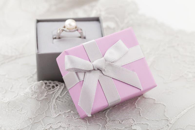 Μικρά ρόδινα κιβώτια δώρων κοσμήματος με το τόξο στο υπόβαθρο δαντελλών στοκ φωτογραφία