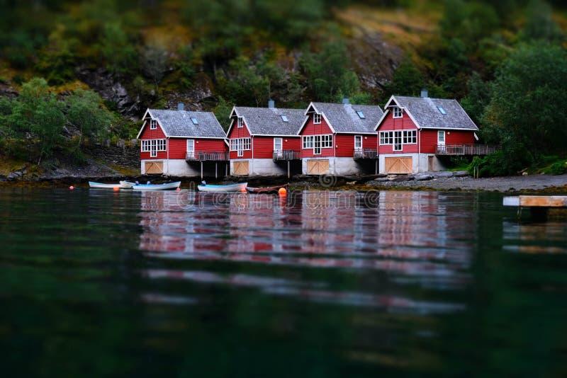 Μικρά σπίτια βαρκών ψαριών σε Flam, Νορβηγία Επίδραση μετατόπισης κλίσης Κλασικές κόκκινες καμπίνες rorbu κοντά στην όχθη ποταμού στοκ φωτογραφίες