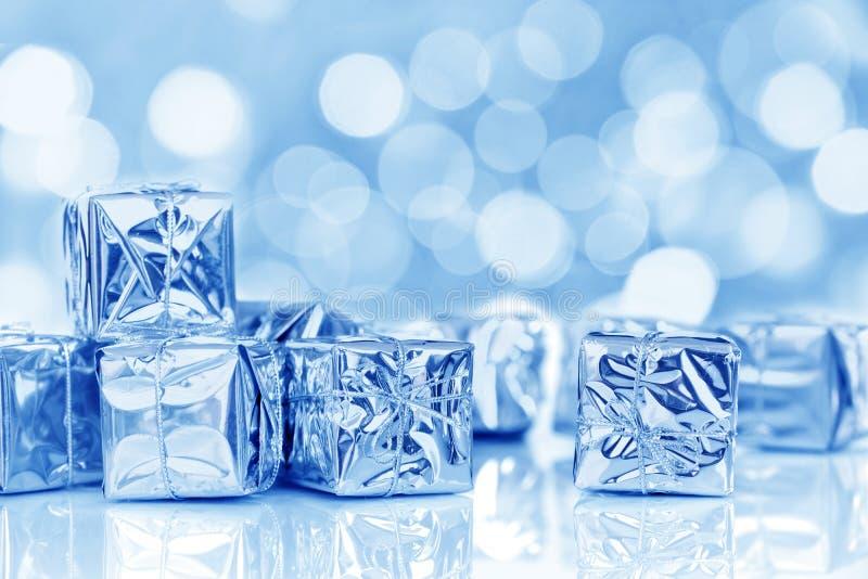Μικρά δώρα Χριστουγέννων στο λαμπρό έγγραφο, μπλε φω'τα bokeh στοκ εικόνες