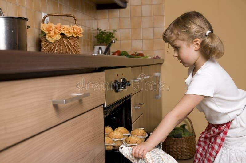 μικρά muffins κοριτσιών ψησίματος στοκ φωτογραφία