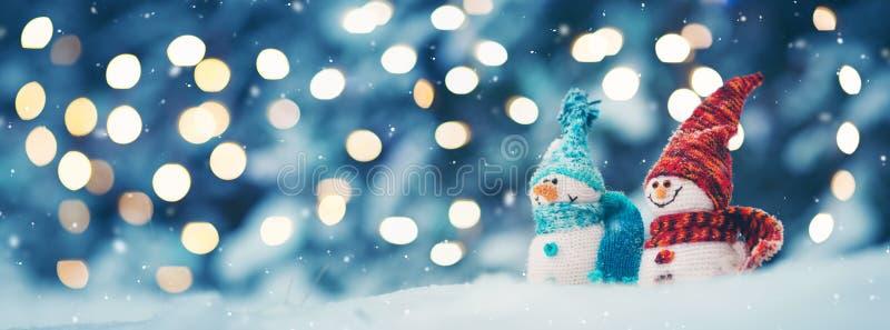 Μικρά snowmans στο μαλακό χιόνι στο μπλε υπόβαθρο στοκ φωτογραφίες με δικαίωμα ελεύθερης χρήσης