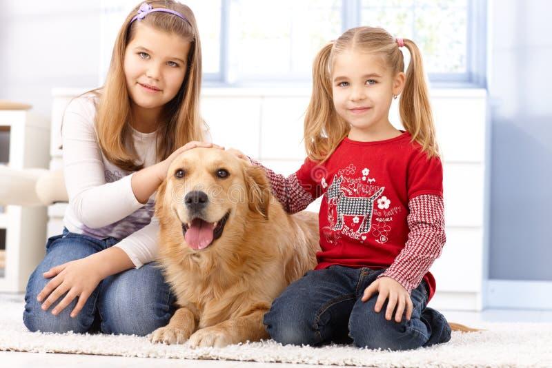 Μικρές αδελφές που χαϊδεύουν το σκυλί στο σπίτι στοκ εικόνες