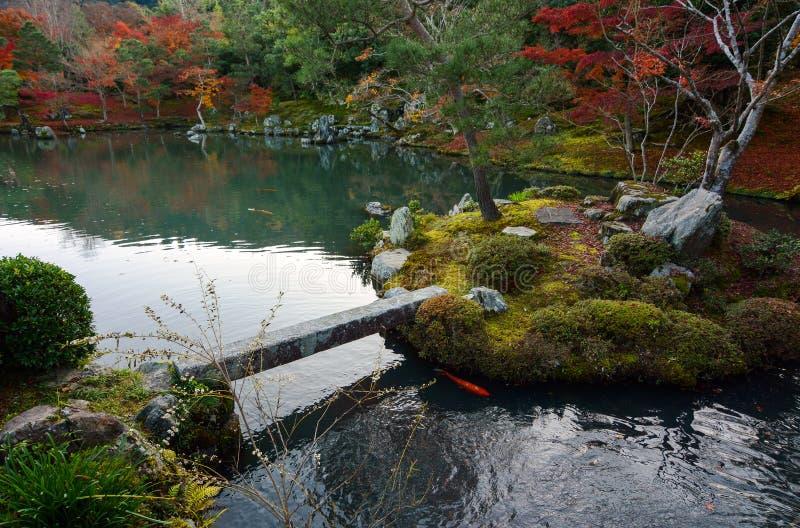 Μικρές νησί και γέφυρα σε μια ειρηνική λίμνη κήπων στην Ιαπωνία κατά τη διάρκεια της πτώσης στοκ φωτογραφία