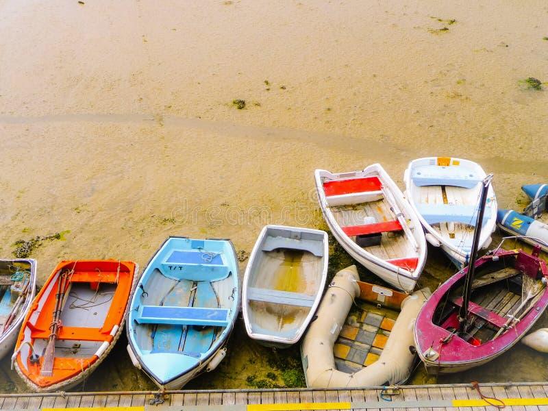 Μικρές παλαιές βάρκες ψαράδων στα διαφορετικά χρώματα που προσαράσσουν στην παραλία στοκ εικόνες