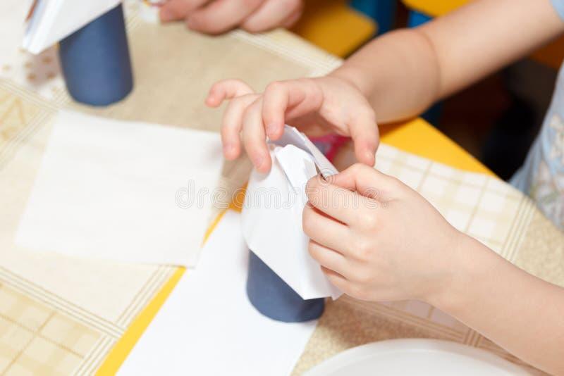 Μικρές τέχνες εγγράφου κόλλας χεριών παιδιών στο σχολικό γραφείο στοκ εικόνα με δικαίωμα ελεύθερης χρήσης