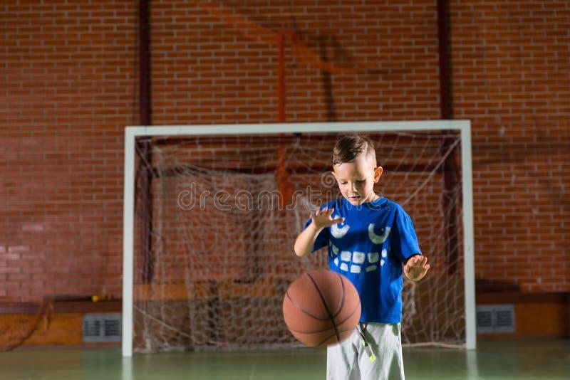 Μικρή άσκηση αγοριών που αναπηδά μια καλαθοσφαίριση στοκ εικόνες