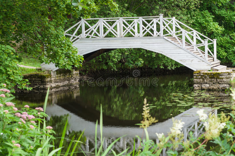 Μικρή λίμνη και διακοσμητική άσπρη ξύλινη γέφυρα στοκ φωτογραφία