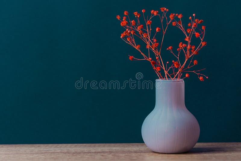 Μικρή ανθοδέσμη των κόκκινων λουλουδιών στο εκλεκτής ποιότητας βάζο στο ξύλινο υπόβαθρο τοίχων επιτραπέζιων μπλε ναυτικών Ορισμέν στοκ εικόνες