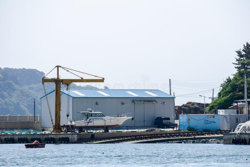 Μικρή αποβάθρα με το εργοστάσιο, το γερανό και την κεκλιμένη ράμπα για τις βάρκες ανελκυστήρων από στοκ φωτογραφία με δικαίωμα ελεύθερης χρήσης