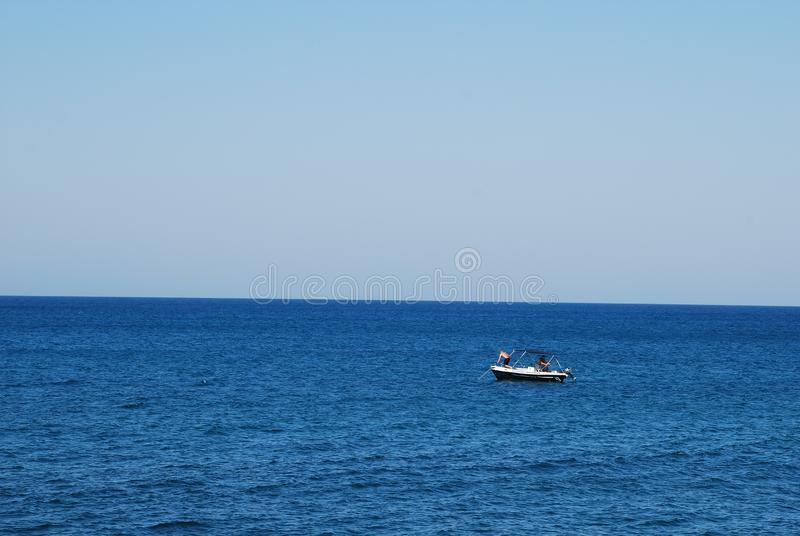 Μικρή βάρκα μηχανών στην μπλε θάλασσα στοκ εικόνα