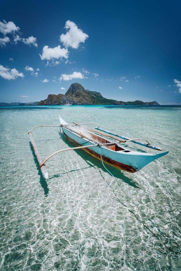 Μικρή βάρκα banca αλιείας μπροστά από το νησί Cadlao στο κρύσταλλο - σαφή ρηχά νερά, χαμηλή παλίρροια, καταπληκτική φύση Palawan στοκ εικόνα