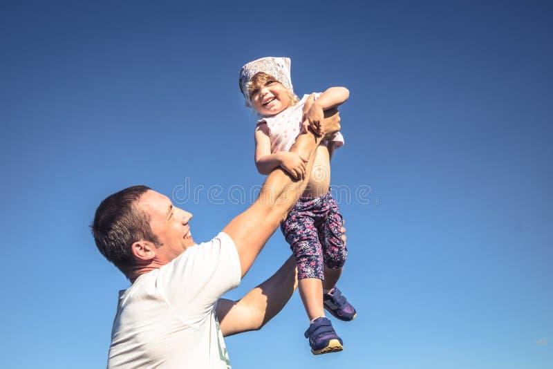 Μικρή διασκέδαση κορών πατέρων ως πορτρέτο οικογενειακού τρόπου ζωής μπροστά από το μπλε ουρανό στοκ φωτογραφίες