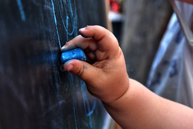 Μικρή εικόνα σχεδίων χεριών κοριτσιών στον πίνακα με την μπλε κιμωλία στοκ εικόνα με δικαίωμα ελεύθερης χρήσης