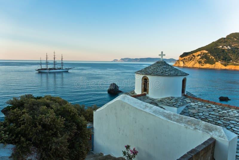 Μικρή εκκλησία και πλέοντας σκάφος στο ηλιοβασίλεμα μπροστά από το λιμάνι πόλεων, νησί της Σκοπέλου στοκ φωτογραφίες με δικαίωμα ελεύθερης χρήσης
