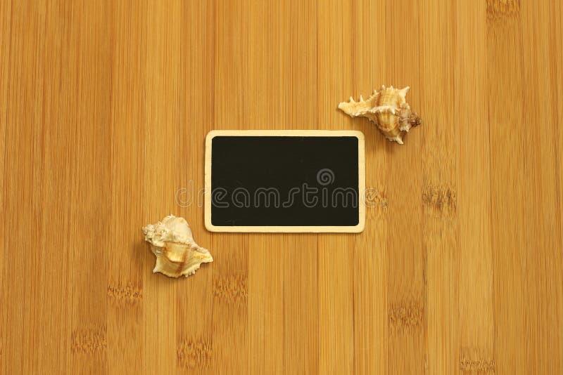 Μικρή κενή πλάκα στο πλάτος για να γράψει ένα μήνυμα που τίθεται στο επίγειο μπαμπού καφετί με τα κοχύλια παραλιών στις πλευρές στοκ φωτογραφία με δικαίωμα ελεύθερης χρήσης