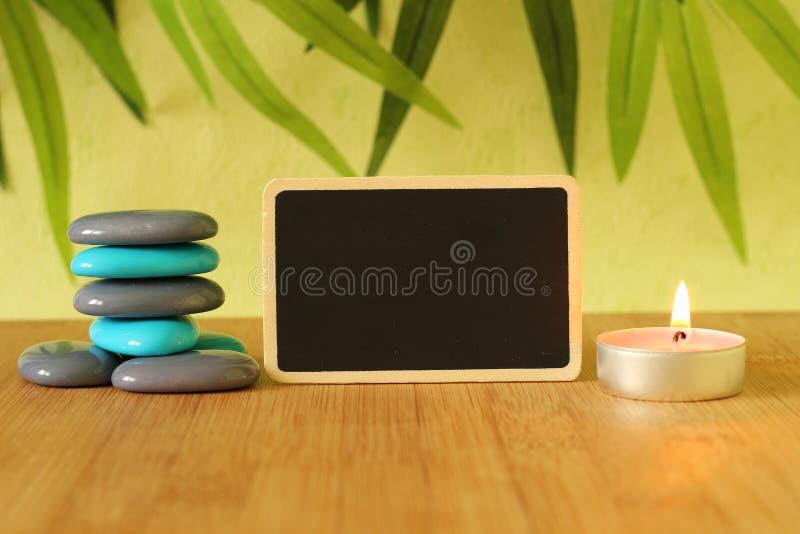 Μικρή κενή πλάκα στο πλάτος για να γράψει ένα μήνυμα που τίθεται στο πάτωμα μπαμπού με τις στήλες γκρίζων και μπλε πετρών στο πνε στοκ εικόνες