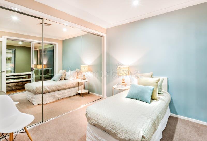Μικρή κρεβατοκάμαρα με τα μαξιλάρια σε ένα ενιαίο κρεβάτι και φω'τα που ανοίγονται τη νύχτα στοκ εικόνα