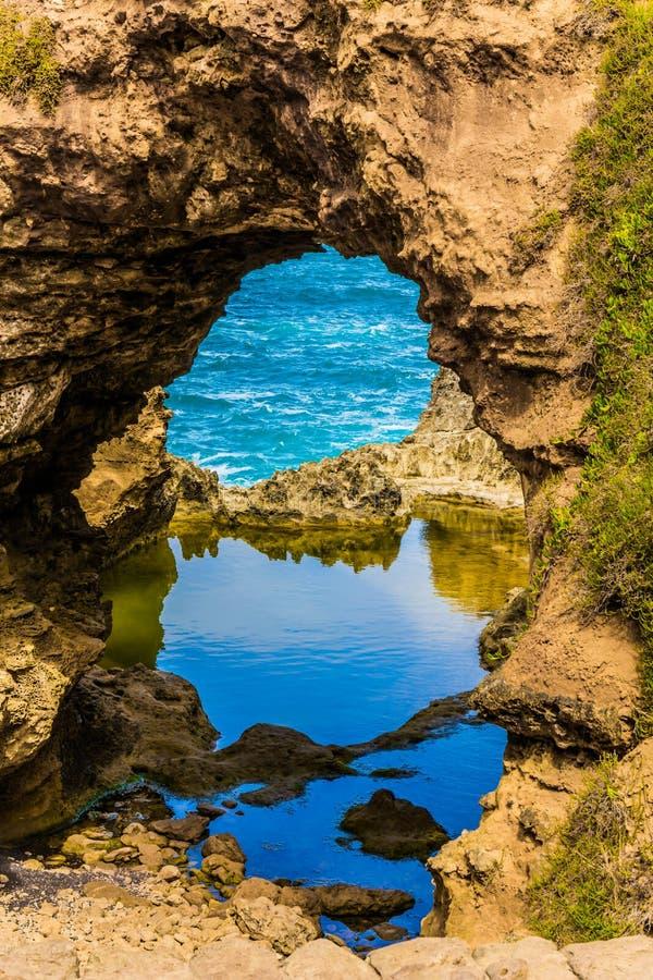 Μικρή λακκούβα του ήρεμου νερού σε μια αψίδα Οι παράκτιοι βράχοι διαμόρφωσαν μια γραφική αψίδα του ψαμμίτη Μεγάλος ωκεάνιος δρόμο στοκ φωτογραφίες