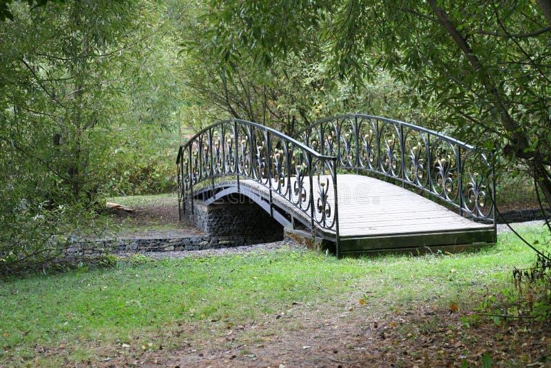 Μικρή λεπτή ξύλινη σχηματισμένη αψίδα γέφυρα πέρα από ένα ήρεμο ρεύμα βαθιά στο παλαιό, παχύ πάρκο διακοπών στοκ φωτογραφία με δικαίωμα ελεύθερης χρήσης