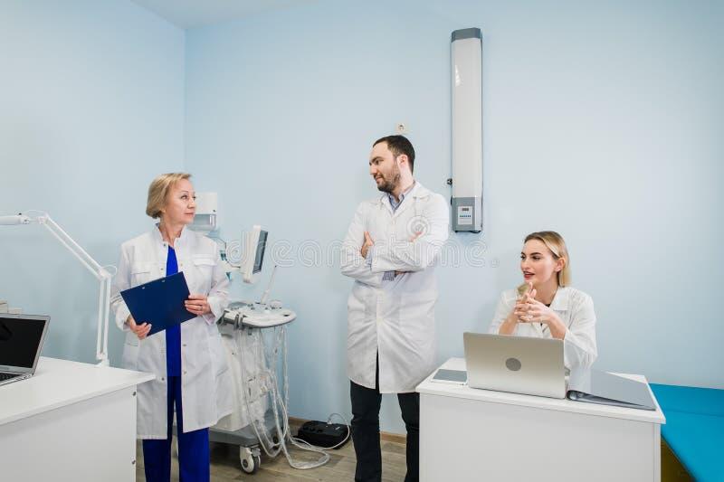 Μικρή ομάδα γιατρών που εργάζονται μαζί στο γραφείο γιατρών ` s στοκ εικόνες