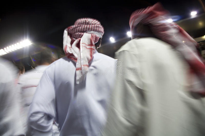 Μικρή ομάδα του Ντουμπάι Ε.Α.Ε. παραδοσιακά ντυμένων μουσουλμανικών ατόμων που περιπλανώνται τους λόγους στο Al Sheba NAD στοκ εικόνες με δικαίωμα ελεύθερης χρήσης