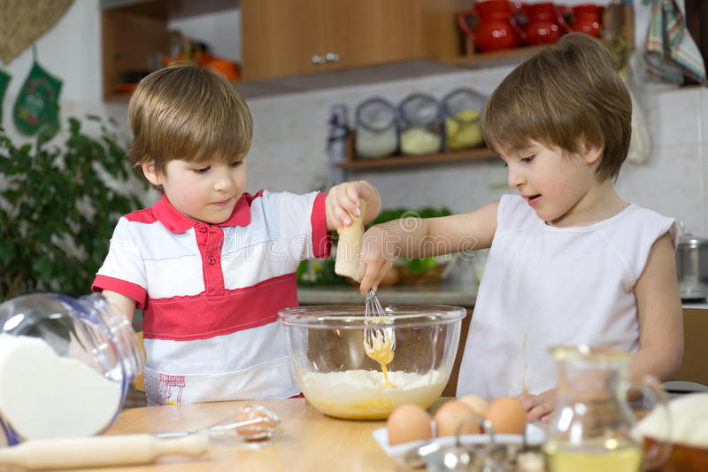 Μικροί δίδυμοι αδερφοί που κατασκευάζουν μια κρέμα για το σπιτικό κέικ στο κύπελλο γυαλιού στοκ εικόνα με δικαίωμα ελεύθερης χρήσης