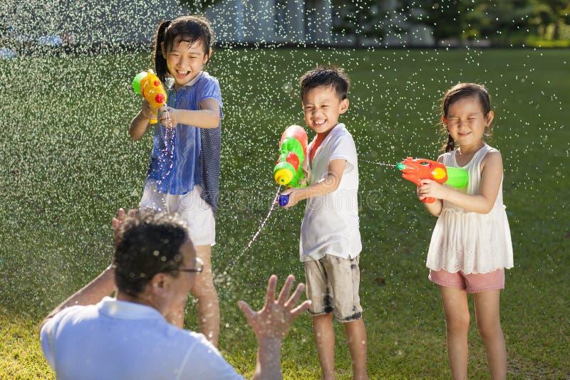 Μικροί τύποι που χρησιμοποιούν τα πυροβόλα όπλα νερού για να ψεκάσει τον πατέρα τους στοκ εικόνα με δικαίωμα ελεύθερης χρήσης