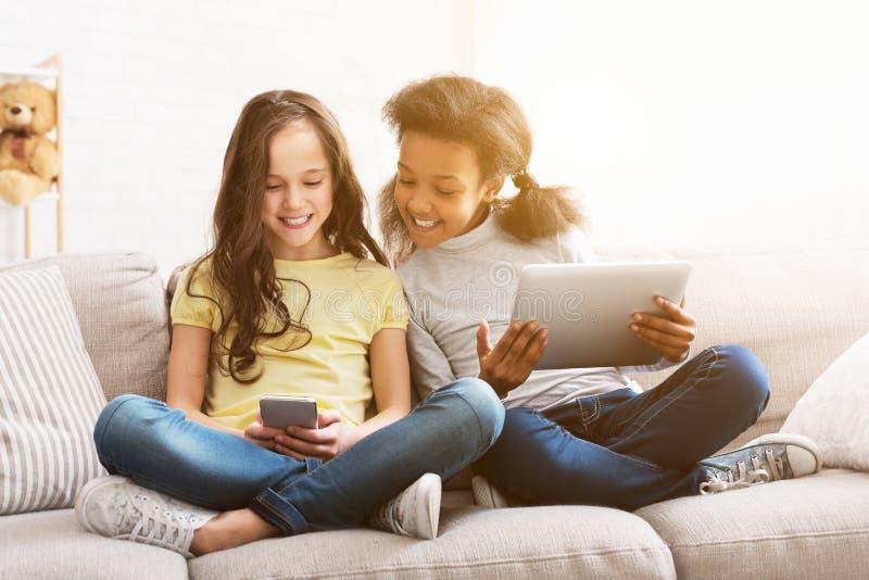 Μικροί φίλοι με τις συσκευές που κάθονται στον καναπέ στο σπίτι στοκ φωτογραφίες