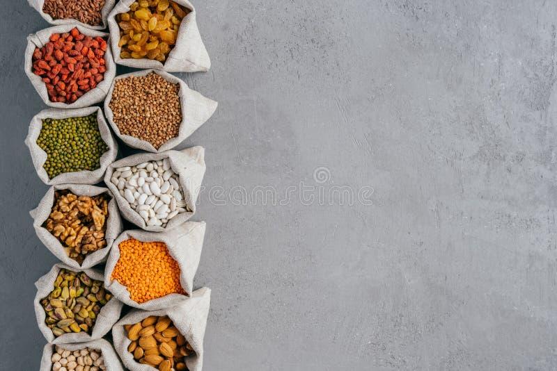 Μικροί burlap σάκοι με το αμύγδαλο, chickpeas, ξύλα καρυδιάς, φαγόπυρο, σταφίδες, goji στο γκρίζο κλίμα με το διάστημα αντιγράφων στοκ εικόνες με δικαίωμα ελεύθερης χρήσης