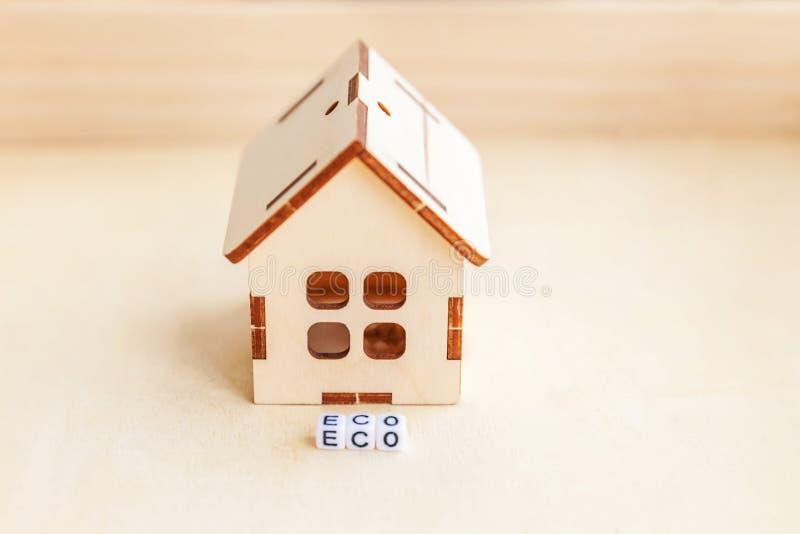 Μικροαρχιτεκτονικό σπίτι μοντέλων παιχνιδιών με επιγραφή Λέξη ECO για ξύλινο φόντο Eco Χωριό, αφηρημένο περιβάλλον στοκ εικόνες