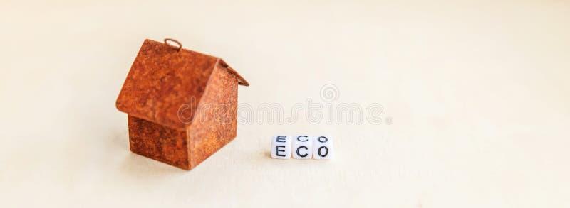 Μικροαρχιτεκτονικό σπίτι μοντέλων παιχνιδιών με επιγραφή Λέξη ECO για ξύλινο φόντο Eco Χωριό, αφηρημένο περιβάλλον στοκ φωτογραφίες με δικαίωμα ελεύθερης χρήσης