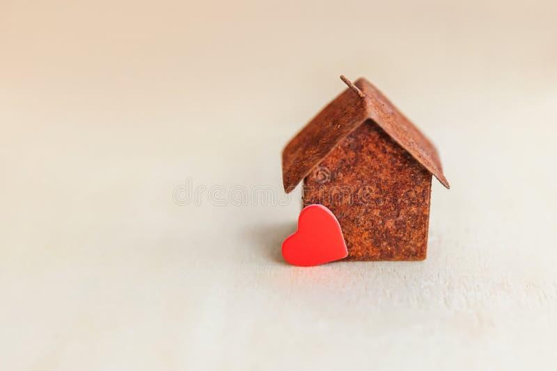 Μικροαρχιτεκτονικό σπίτι μοντέλων παιχνιδιών με κόκκινη καρδιά σε ξύλινο φόντο Οικολογικό Χωριό Στεγαστικά δάνεια στοκ εικόνες