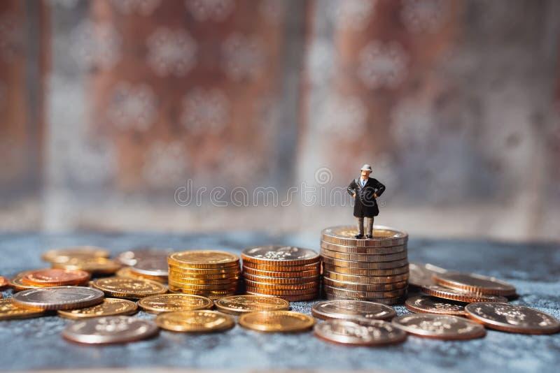 Μικρογραφία, επιχειρηματίας που στέκεται πάνω σε ένα σωρό νομίσματα χρησιμοποιώντας ως οικονομική ιδέα, έννοια συνταξιοδότησης κα στοκ εικόνες
