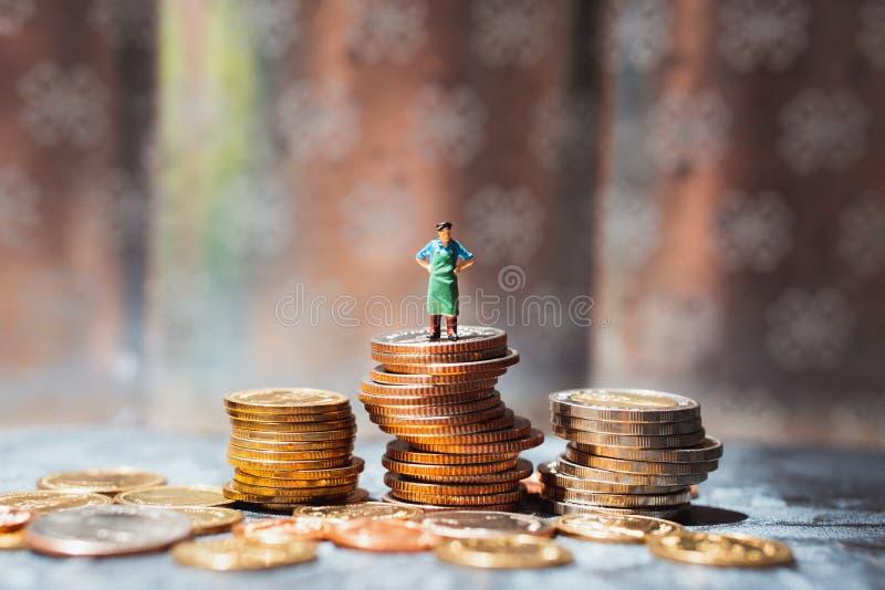 Μικρογραφία, εργαζόμενος που στέκεται πάνω σε ένα σωρό νομίσματα χρησιμοποιώντας την υλικοτεχνική, επιχειρηματική και οικονομική  στοκ εικόνες