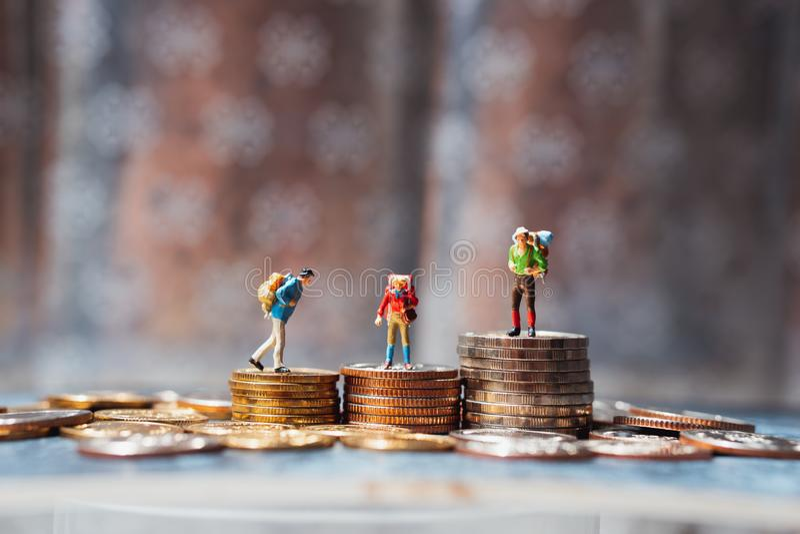 Μικρογραφία, ομάδα ταξιδιωτών που στέκονται πάνω σε στοίβες με κέρματα που χρησιμοποιούνται ως επιχειρηματικός ανταγωνισμός και ο στοκ φωτογραφία με δικαίωμα ελεύθερης χρήσης