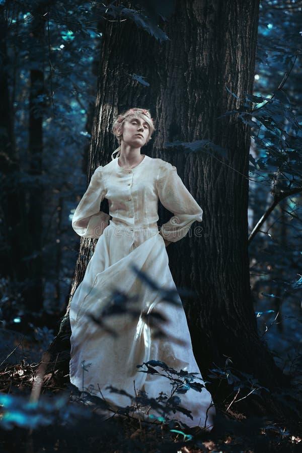 Μικροκαμωμένο κορίτσι σε ένα δάσος σεληνόφωτου στοκ εικόνα με δικαίωμα ελεύθερης χρήσης