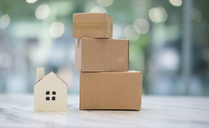 Μικροσκοπικά σπίτι και κουτιά από χαρτόνι, έννοια του νέου σπιτιού κίνησης στοκ εικόνα