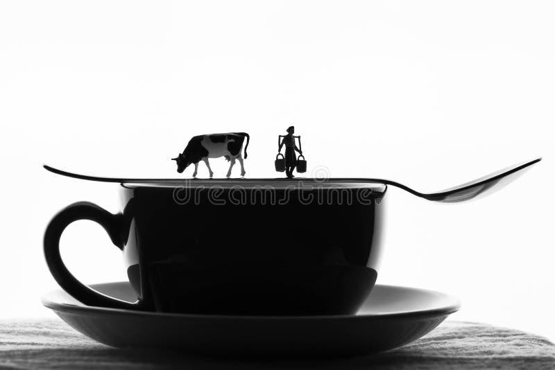 Μικροσκοπικές γυναίκα και αγελάδα σε ένα φλυτζάνι καφέ στοκ φωτογραφία