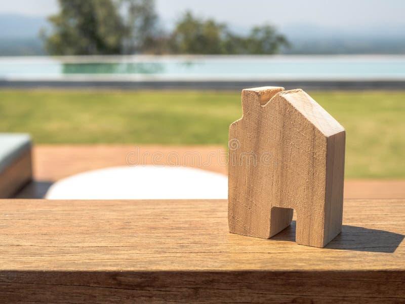 Μικροσκοπική ξύλινη χλεύη σπιτιών επάνω πέρα από τη θολωμένη πράσινη χλόη την ημέρα Εικόνα για την έννοια επένδυσης ακίνητων περι στοκ φωτογραφίες