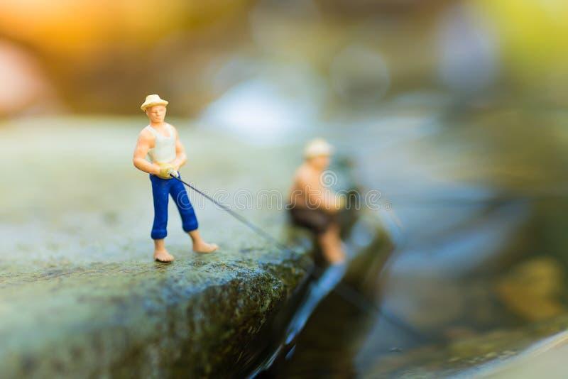 Μικροσκοπική συνεδρίαση ψαράδων στην πέτρα, που αλιεύει στον ποταμό Μακρο φωτογραφία άποψης, χρήση ως έννοια σταδιοδρομίας αλιεία στοκ φωτογραφία με δικαίωμα ελεύθερης χρήσης