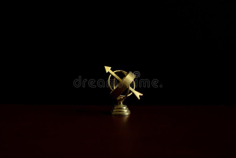 Μικροσκοπική χρυσή παλαιά σφαίρα αστρολάβων στο σκοτάδι στοκ εικόνα με δικαίωμα ελεύθερης χρήσης
