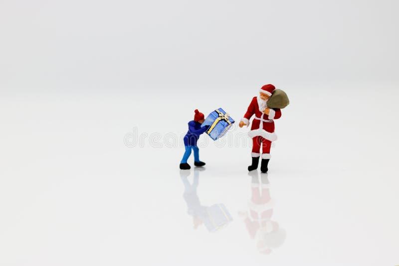 Μικροσκοπικοί άνθρωποι: Άγιος Βασίλης και παιδιά με το δώρο στοκ φωτογραφία