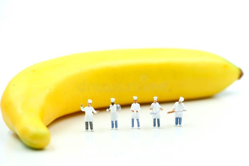 Μικροσκοπικοί άνθρωποι: Αρχιμάγειρας κατά τη διάρκεια του μαγειρέματος και της εργασίας με την μπανάνα στοκ εικόνες με δικαίωμα ελεύθερης χρήσης