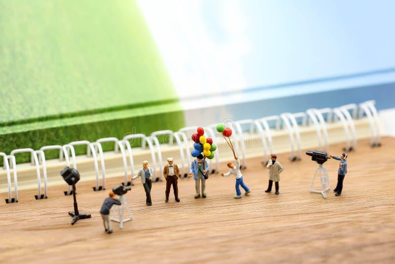 Μικροσκοπικοί άνθρωποι: δημοσιογράφοι, καμεραμάν, Videographer στην εργασία στοκ φωτογραφία