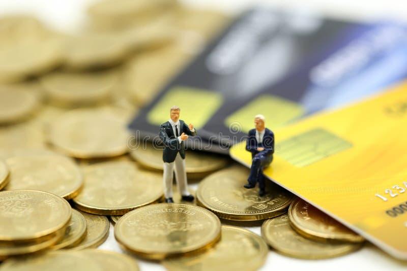 Μικροσκοπικοί άνθρωποι: επιχειρηματίας με τα νομίσματα πιστωτικών καρτών και σωρών, την υποχρέωση, τη συμφωνία, την επένδυση, την στοκ εικόνες