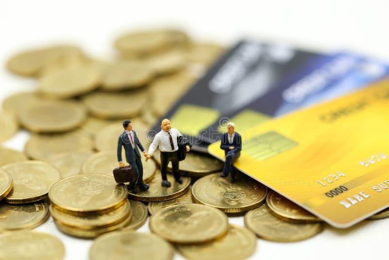 Μικροσκοπικοί άνθρωποι: επιχειρηματίας με τα νομίσματα πιστωτικών καρτών και σωρών, την υποχρέωση, τη συμφωνία, την επένδυση, την στοκ φωτογραφίες με δικαίωμα ελεύθερης χρήσης